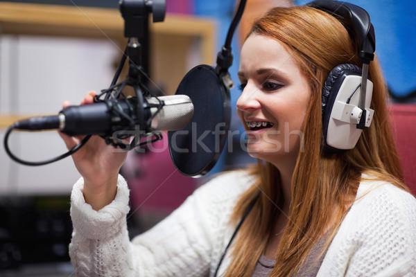 Happy radio host speaking through a microphone Stock photo © wavebreak_media