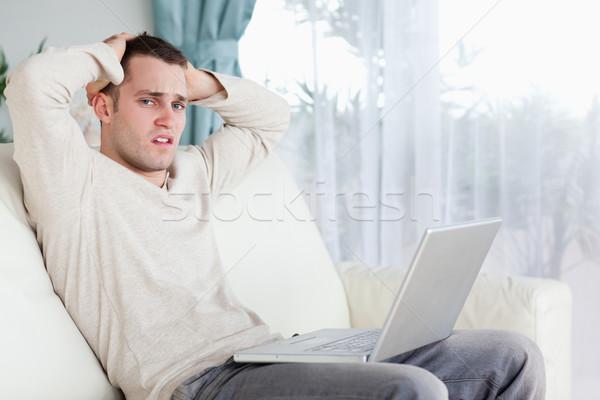 Sad man working with his laptop in his living room Stock photo © wavebreak_media
