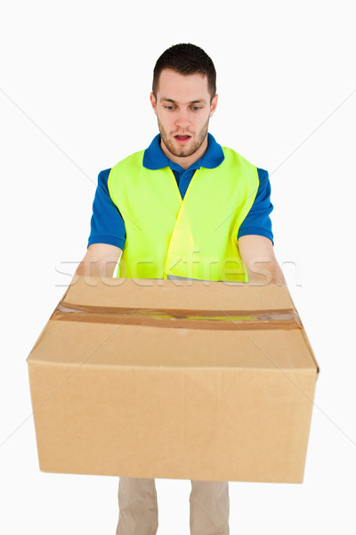 Surprised looking delivery man handing over parcel against a white background Stock photo © wavebreak_media