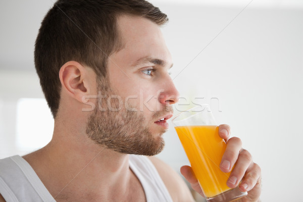 Close up of a healthy man drinking orange juice in his kitchen Stock photo © wavebreak_media