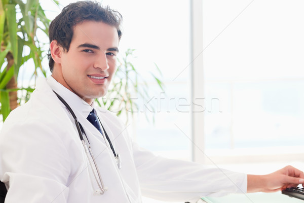 Zijaanzicht jonge arts vergadering achter bureau Stockfoto © wavebreak_media