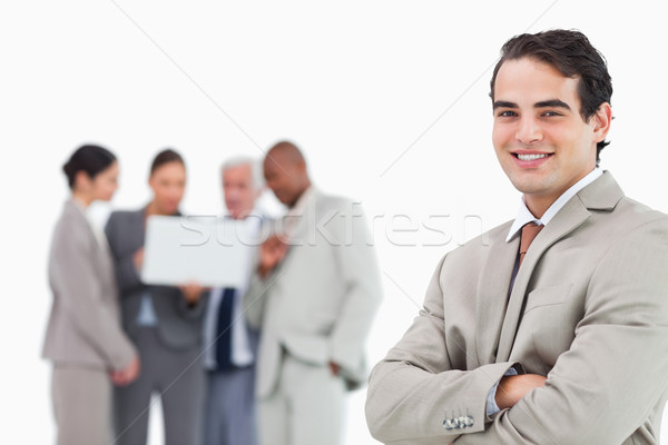 Smiling salesman with arms folded and colleagues behind him against a white background Stock photo © wavebreak_media