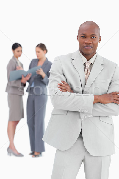Businessman with crossed arms and colleagues behind him against a white background Stock photo © wavebreak_media
