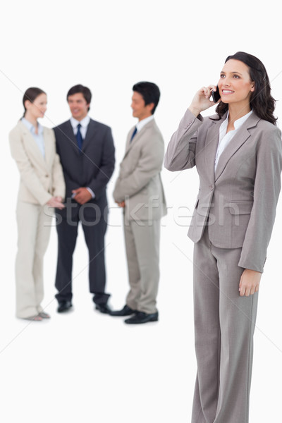Saleswoman on the cellphone with team behind her against a white background Stock photo © wavebreak_media