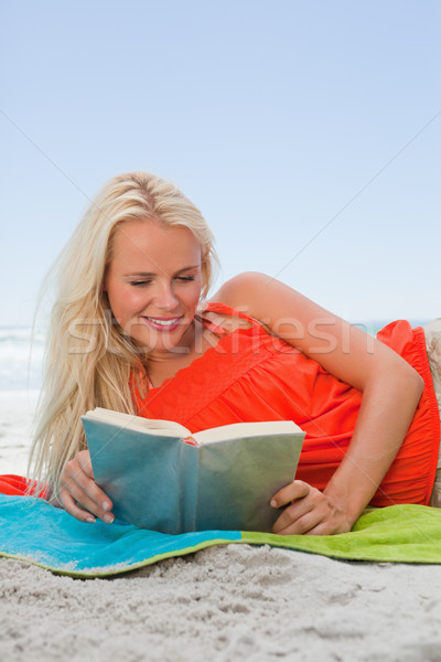 Young smiling woman lying on her beach towel while reading a book Stock photo © wavebreak_media