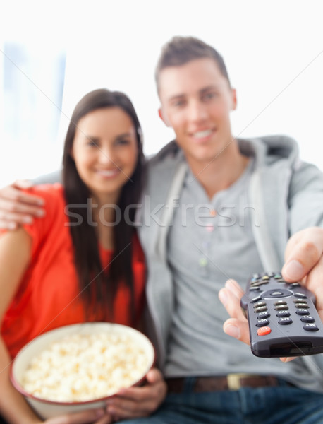 A close up shot focused on the tv remote in the man's hand as he sits with his girlfriend on the cou Stock photo © wavebreak_media