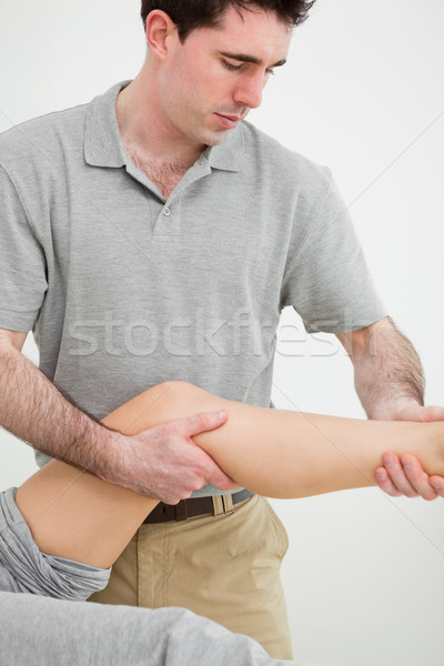Serious osteopath examining a the leg of his patient in a room Stock photo © wavebreak_media