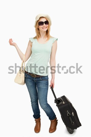 Cheerful woman leaning on a suitcase while sitting against white background Stock photo © wavebreak_media