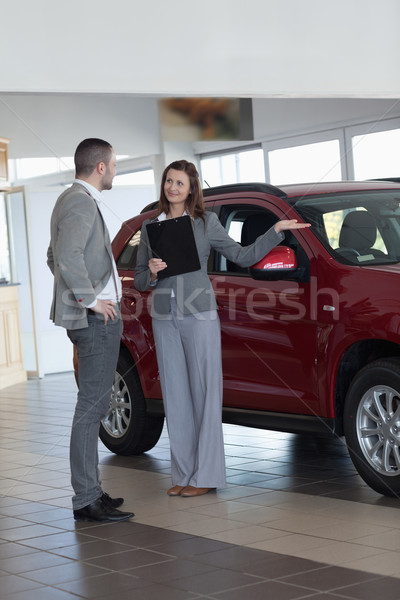 Stock photo: Businesswoman showing a car in a dealership