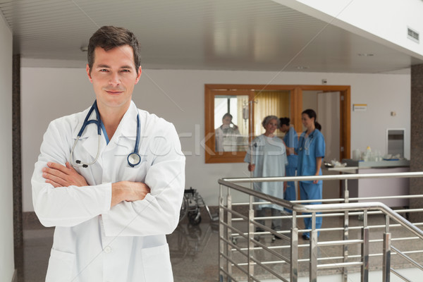 Smiling doctor standing in the hallway of a hospital while crossing his arms Stock photo © wavebreak_media