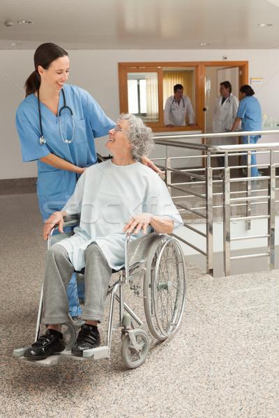 Nurse smiling at old women sitting in wheelchair in hospital corridor Stock photo © wavebreak_media