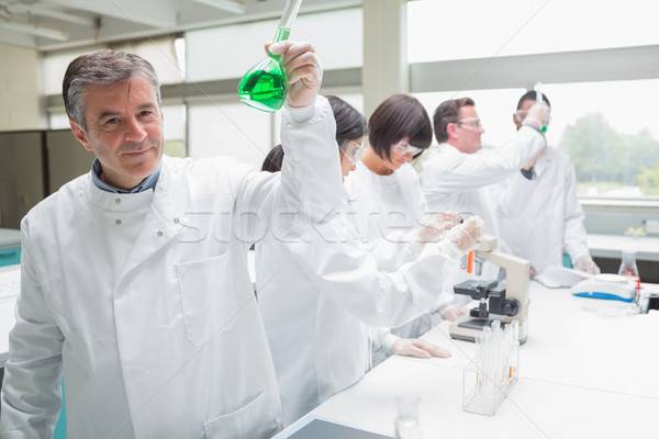 Chemist raising beaker of green liquid in busy lab Stock photo © wavebreak_media