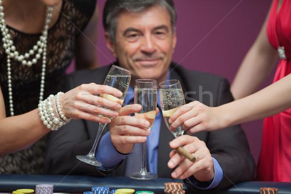 Sorridente homem sessão cassino óculos mulheres Foto stock © wavebreak_media
