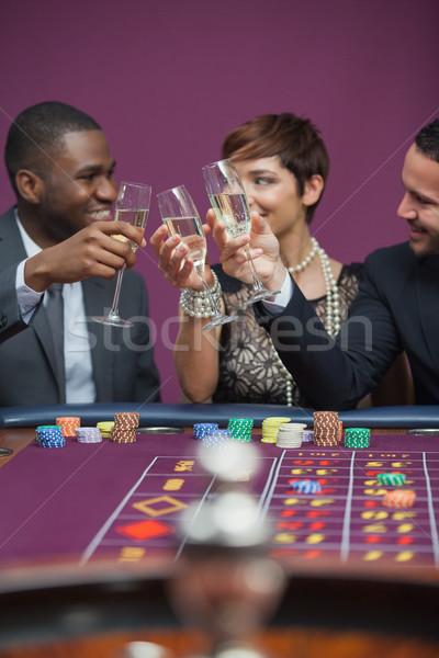 Tres personas jugando ruleta sesión mesa Foto stock © wavebreak_media