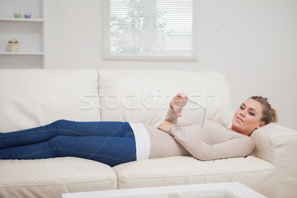 Woman relaxing on the couch while holding a pane as a tablet pc and smiling Stock photo © wavebreak_media