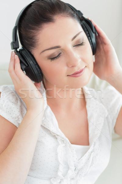 笑顔の女性 着用 ヘッドホン 音楽を聴く 座って ソファ ストックフォト © wavebreak_media