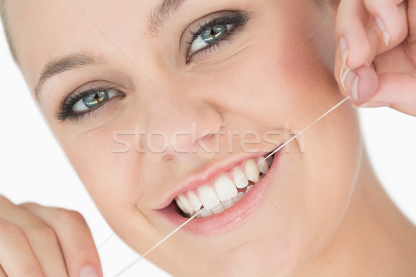 Woman using dental floss in the white background Stock photo © wavebreak_media