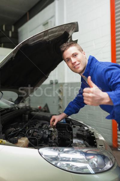 Auto mechanic by car gesturing thumbs up Stock photo © wavebreak_media
