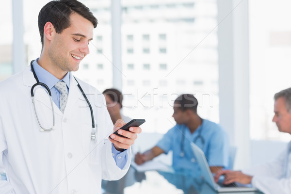 Doctor text messaging with group around table in hospital Stock photo © wavebreak_media