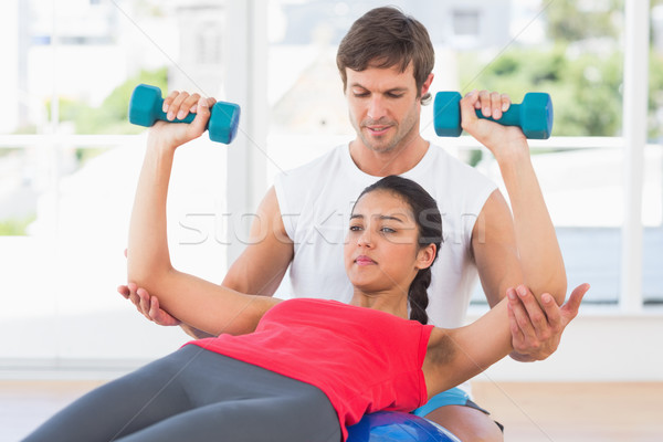 Instructor assisting woman with dumbbell weights Stock photo © wavebreak_media