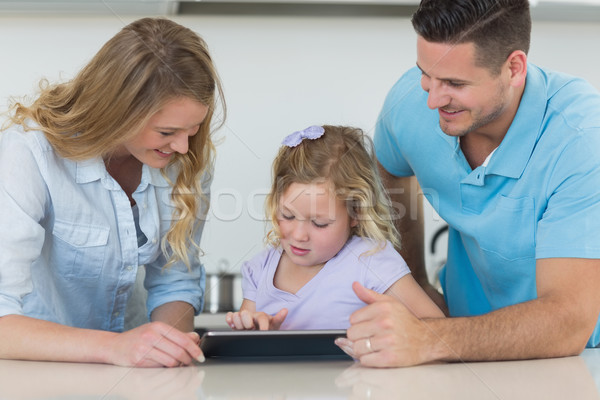 Stock photo: Family using tablet PC at table