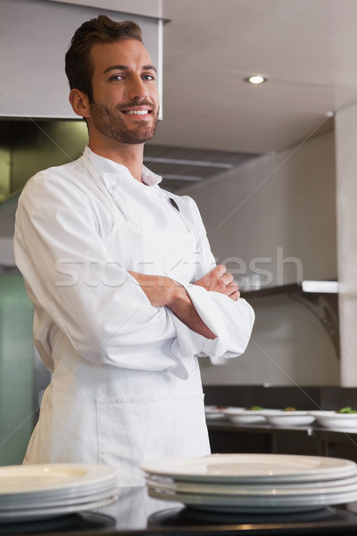 Happy young chef standing with arms crossed behind counter Stock photo © wavebreak_media