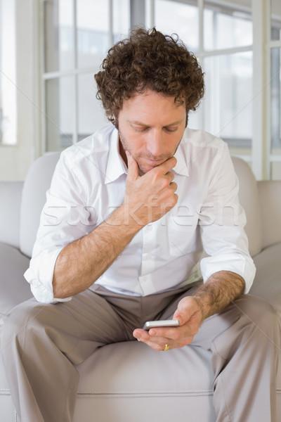 Nyugodt férfi sms üzenetküldés otthon fiatalember kanapé Stock fotó © wavebreak_media