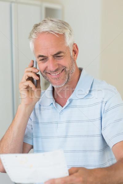 Mosolyog férfi telefonbeszélgetés otthon konyha asztal Stock fotó © wavebreak_media