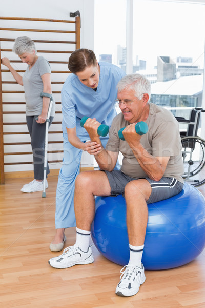 Therapist assisting senior man with dumbbells Stock photo © wavebreak_media