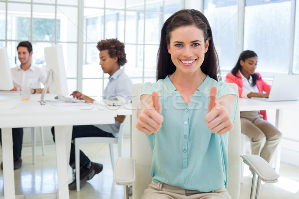 Attractive worker gives two thumbs up to camera Stock photo © wavebreak_media