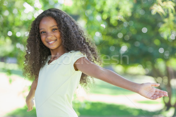 Young girl smiling at the camera with arms outstretched Stock photo © wavebreak_media