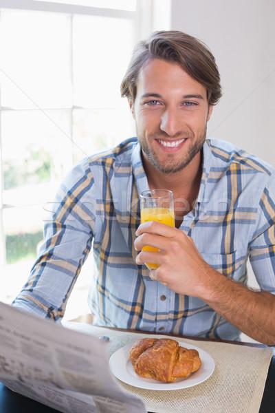 Casual sorridente homem suco de laranja leitura jornal Foto stock © wavebreak_media