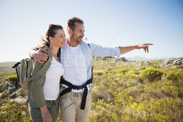 Hiking couple pointing and smiling on country terrain Stock photo © wavebreak_media