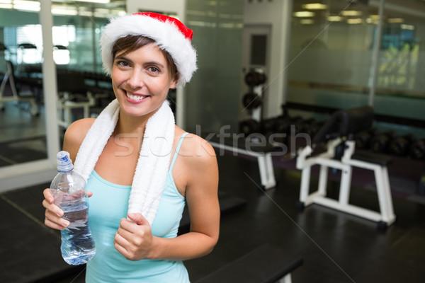 Dopasować brunetka Święty mikołaj hat uśmiechnięty kamery Zdjęcia stock © wavebreak_media