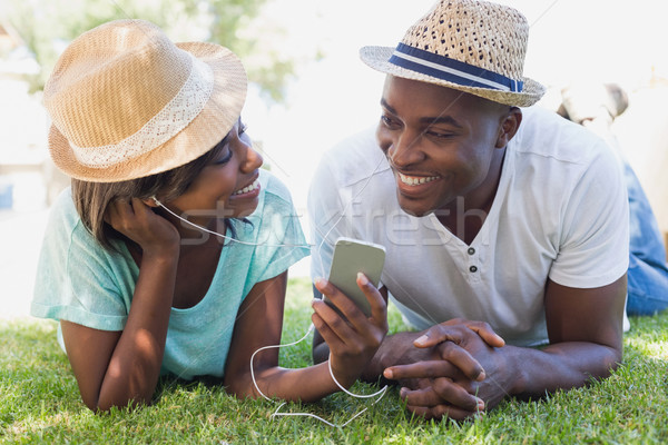 Happy couple lying in garden together listening to music Stock photo © wavebreak_media