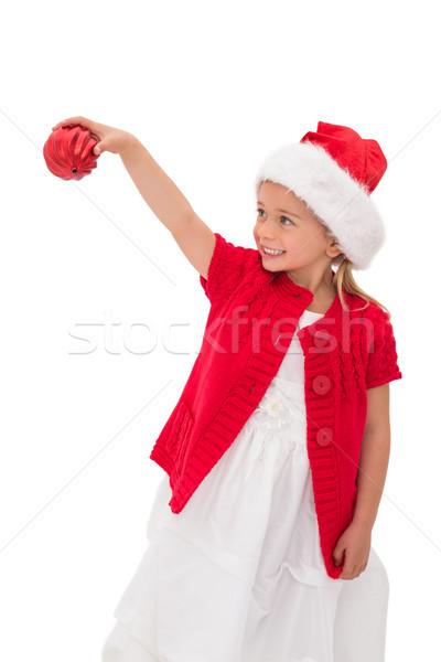 Cute little girl wearing santa hat holding bauble Stock photo © wavebreak_media