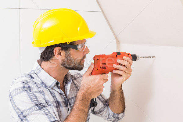 Construction worker drilling hole in wall Stock photo © wavebreak_media