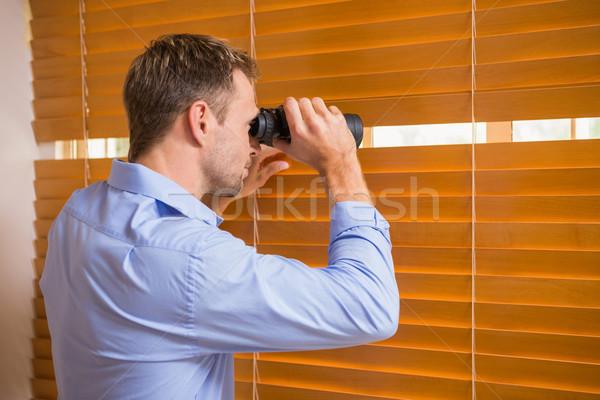 Man looking with binoculars through the blinds Stock photo © wavebreak_media