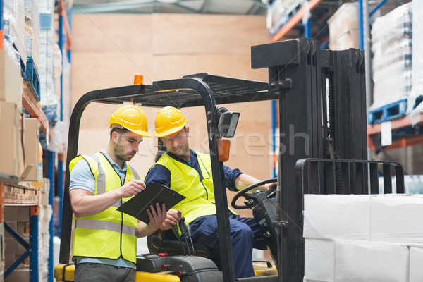 Warehouse worker talking with forklift driver Stock photo © wavebreak_media