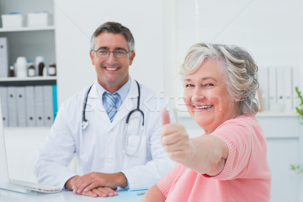 Patient showing thumbs up sign while sitting with doctor Stock photo © wavebreak_media