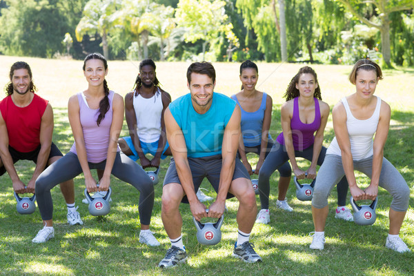 Fitness group squatting in park with kettle bells  Stock photo © wavebreak_media