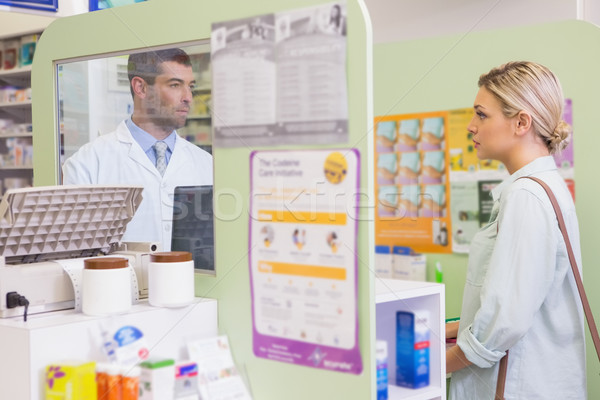 Pharmacist speaking with cheerful young customer Stock photo © wavebreak_media