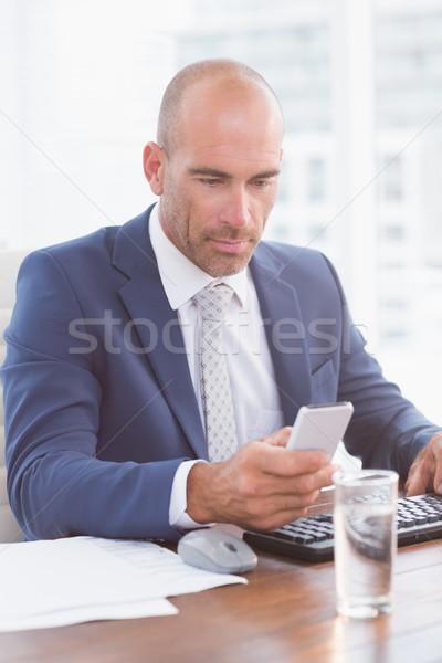 Businessman using his smartphone Stock photo © wavebreak_media