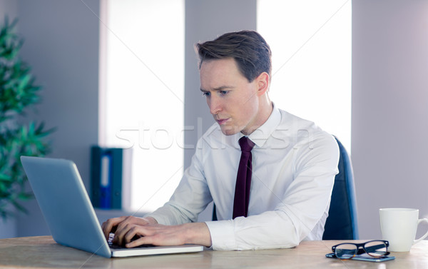 Serious businessman typing on laptop Stock photo © wavebreak_media