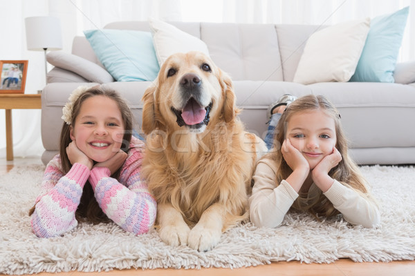 Sisters lying on rug with golden retriever smiling at camera Stock photo © wavebreak_media