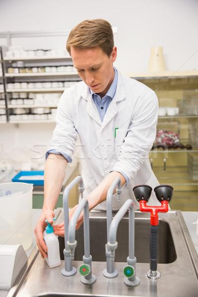 Handsome pharmacist washing his hands Stock photo © wavebreak_media