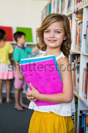 Student covering face with book in library  Stock photo © wavebreak_media