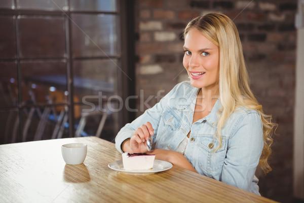 Smiling blonde eating cake and having coffee Stock photo © wavebreak_media