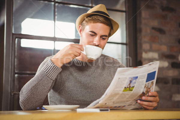 Handsome hipster drinking coffee and reading newspaper Stock photo © wavebreak_media