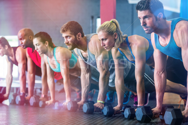 People doing push ups with dumbbell in gym Stock photo © wavebreak_media